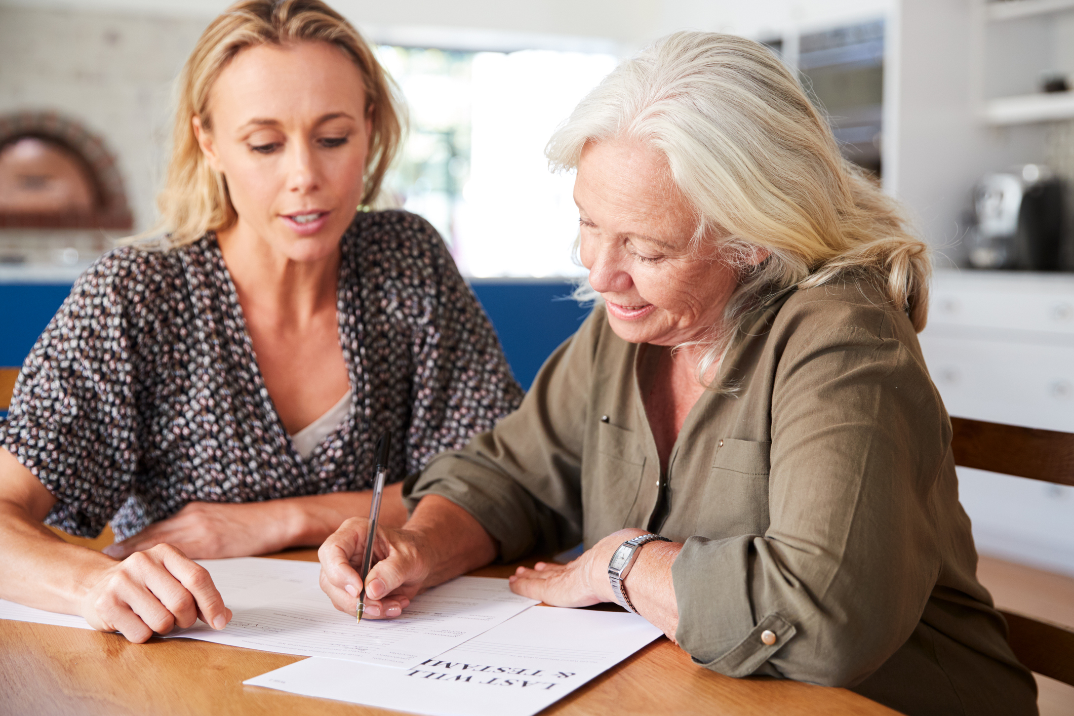 Younger Woman helping Older Woman fill out Last Will