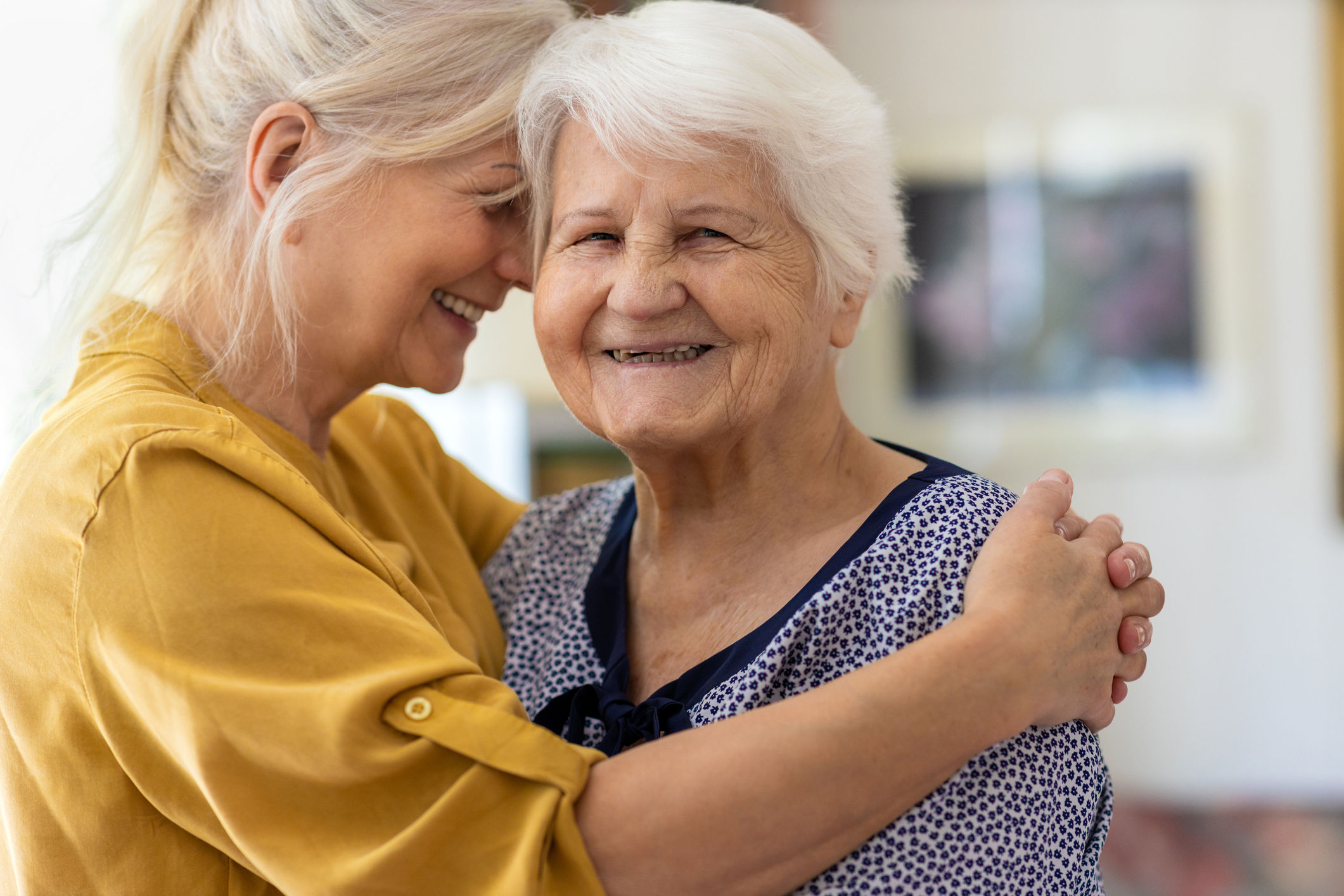 Woman embracing her elderly mother